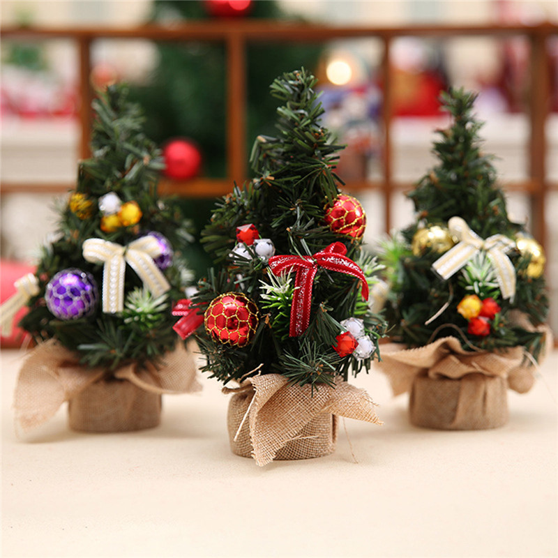 three small christmas trees with hessian pots on a table